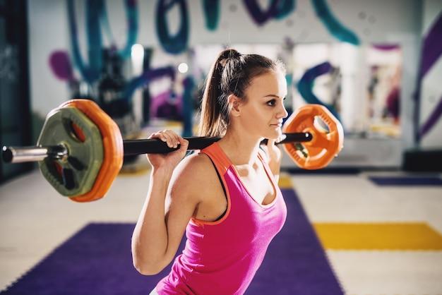 Красивая молодая девушка формы фитнеса делая приседания с штангой в спортзале.