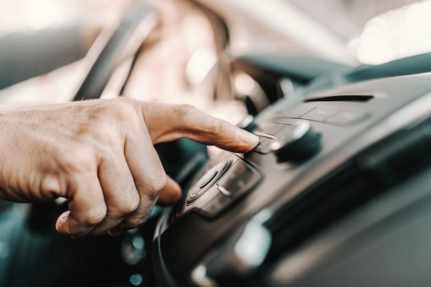 Старший человек, смена радиостанции, сидя в своей машине.