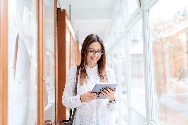 掲示板の横に立っていると大学の建物に立っている間タブレットを使用して美しい白人ブルネット。