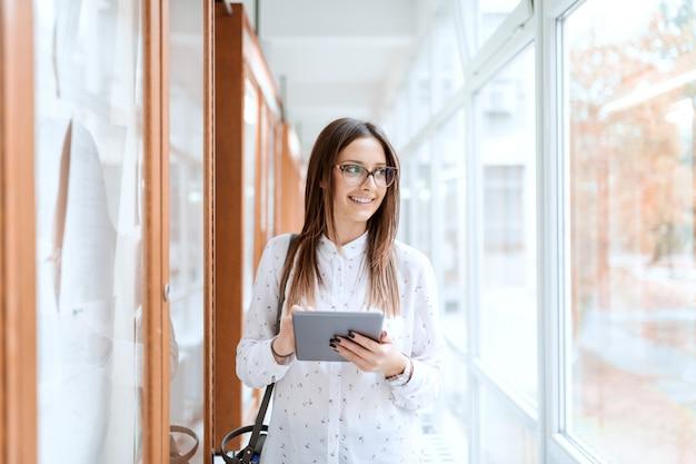 掲示板の横にある美しい白人ブルネットと大学の建物に立って、トラフウィンドウを探しながらタブレットを使用しています。