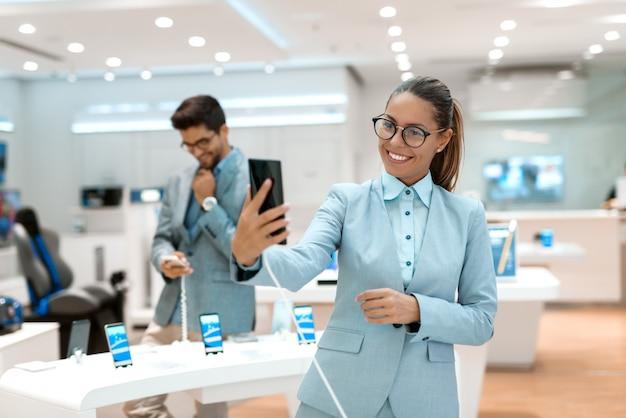 Счастливая кавказская женщина принимая автопортрет с новым умным телефоном пока стоящ в техническом магазине. на заднем плане ее муж опробовал смартфон. технический магазин интерьера.