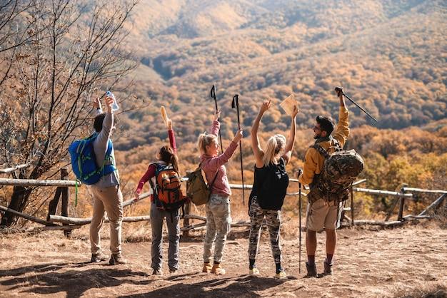 Счастливые туристы, стоя на поляне с руками в воздухе и наслаждаясь видом. спиной повернулся. осеннее время