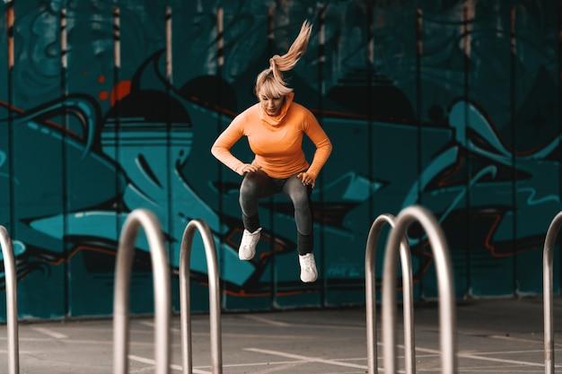 Молодая красивая блондинка кавказская женщина в спортивной одежде и с хвостиком, прыжки под мостом. полная длина.