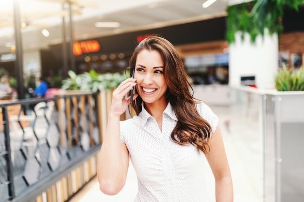 ショッピングモールでスマートフォンを使用してカジュアルな服を着て長い茶色の髪を持つ魅力的な白人女性の肖像画。