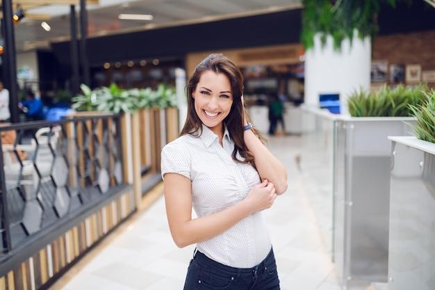Три четверти длины потрясающей кавказской брюнетки в рубашке, позирует в торговом центре.