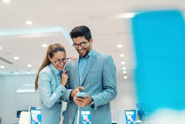 かわいい多文化のカップルは、テックストアで新しいスマートフォンを選択するエレガントな服を着ています。スマートフォンを指している男。