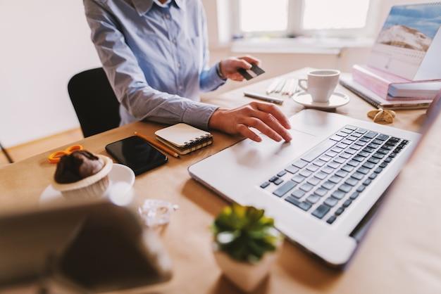 ノートパソコンで若い女性デザイナーの手のクローズアップ。ガジェットを備えたデザイナーデスク。