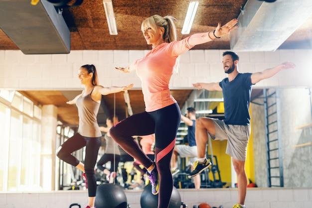 Тренер показывая к упражнению баланса группы в спортзале. на заднем плане их зеркальное отражение.