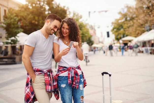 通りに立っている間スマートフォンで写真を見て笑顔のカップル。旅行の概念。