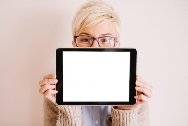 きれいな女性がそれを保持しながら、白い編集可能な画面で水平位置にあるタブレットのフォーカスビューを閉じます。
