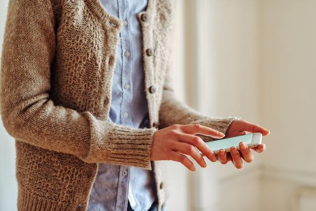 白い電話を保持している女の子の手の側面図です。