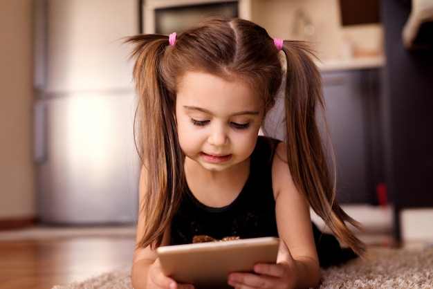 ゴージャスな子が床に横たわっている間タブレットで遊んでポニーテールを持つ少女。