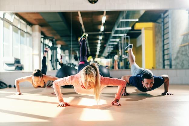 ジムの床で筋力トレーニングを行う健康的な習慣を持つスポーティな人々のグループ。バックグラウンドミラー。