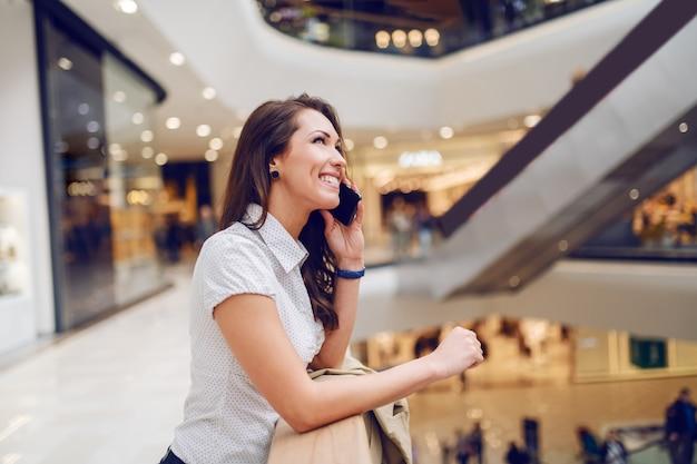 手すりにもたれて、電話で話している見事な笑顔のブルネット。ショッピングモールのインテリア。