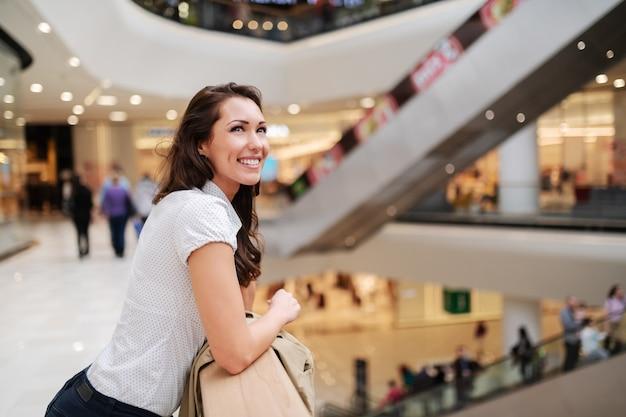 手すりと見上げるにもたれて見事な歯を見せる笑顔で美しい白人ブルネット。ショッピングモールのインテリア。