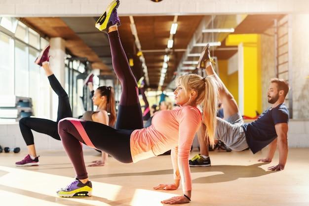 ジムの床でフロントキック運動を行うスポーツウェアの人々の健康的なスポーティな小グループのグループ。バックグラウンドミラー。