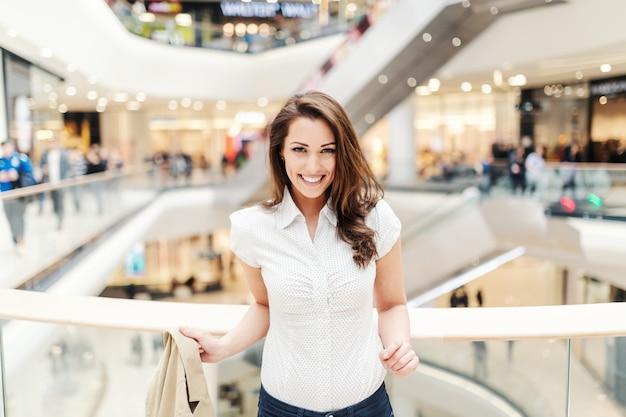 こぼれるような笑顔で美しい白人女性は、ショッピングモールでカジュアルなポーズを着ています。