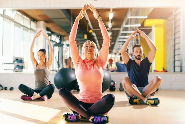 足を組んで体育館の床に座ってリラクゼーション運動をしているフィットする人々の小さなグループ。バックグラウンドミラー。