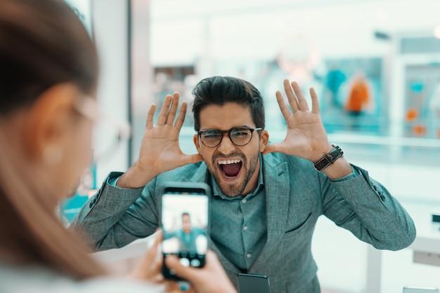 テックストアで新しいスマートフォンを試すカップル。ふざけている夫の写真を撮る女性。
