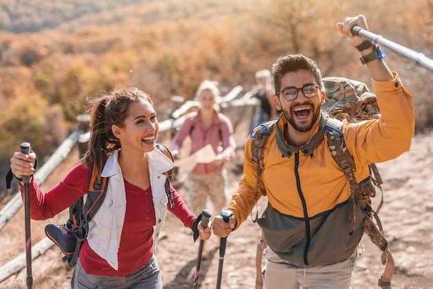 Группа счастливых туристов, гуляющих по поляне и болтающих. на переднем плане пара, ведущая группу. осеннее время