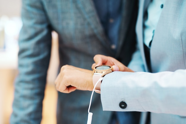 テックストアに立っている間新しい腕時計をしようとしている女性のクローズアップ。