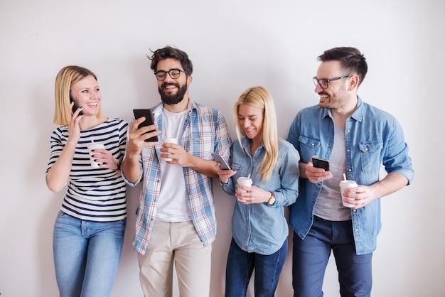 スマートフォンを使用して、壁に立っている間行くコーヒーを保持している若い人たちのグループ。ビジネスコンセプトを開始します。