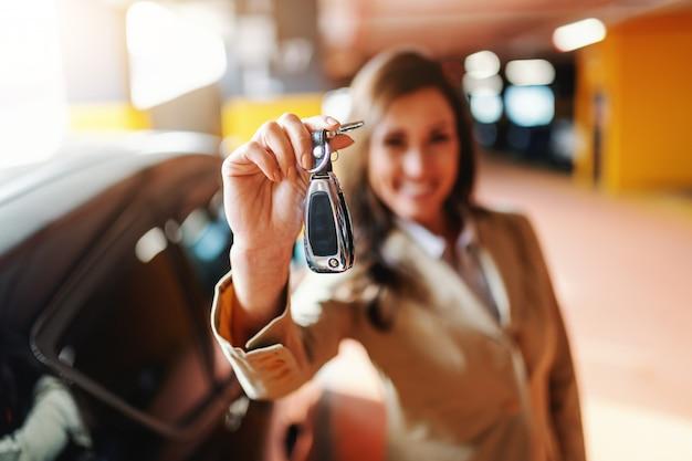 駐車場で車のキーを保持している笑顔の美しいブルネットのクローズアップ。キーを手にセレクティブフォーカス。