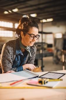 ワークショップで青写真とタブレットを扱う眼鏡の魅力的な笑みを浮かべてやる気のある中年産業女性エンジニアのクローズアップ表示。