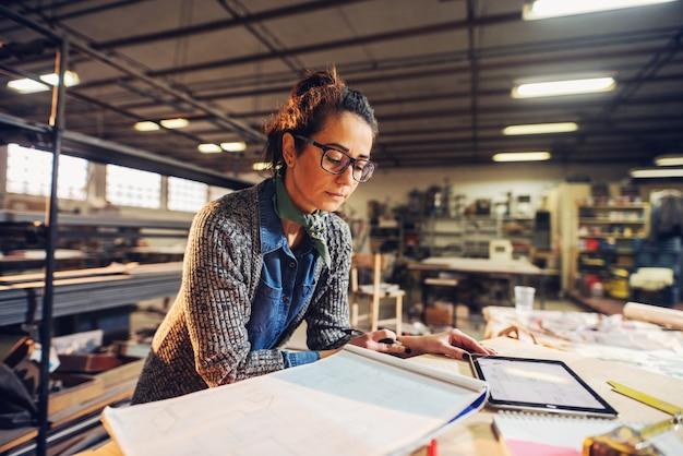 中年の彼女のワークショップでプロジェクトに取り組んでいる眼鏡の美しい女性エンジニア。