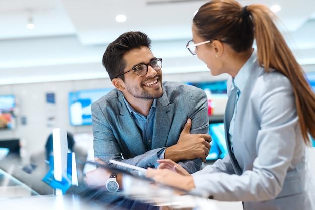 ハイテク店に立ちながら購入する新しいタブレットを探しているビジネス服を着た多文化のカップル。タブレットと組んだ腕で立っている男性を保持している女性。