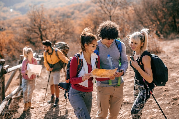 Туристы, глядя на карту, стоя на поляне.