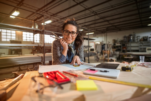 新しいプロジェクトに取り組んでいる彼女のワークショップで美しい焦点を当てた中年女性建築家の写真。カメラを見て、笑顔。