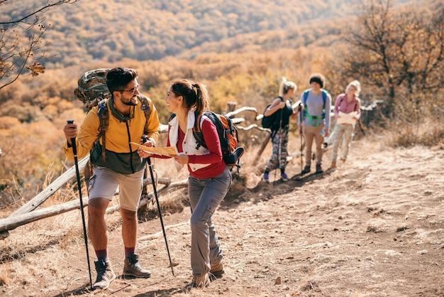 秋のハイキングの小さなグループ。マップを見ている前景のカップルと、グループの残りの背景。
