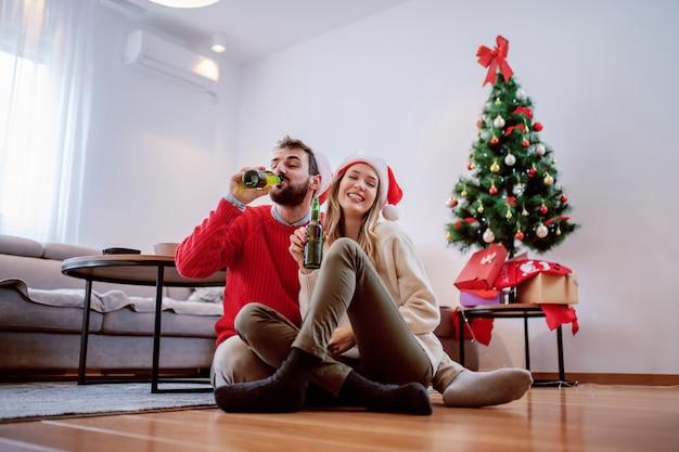 床に座ってビールを飲みながら頭にサンタの帽子を持つ陽気なハンサムな白人カップル。背景にはクリスマスツリーがあります。リビングルームのインテリア。