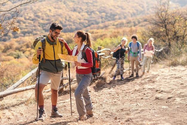 笑顔のブルネットの地図を押しながら友達に寄りかかっています。バックグラウンドでグループの残りの部分。秋のコンセプトで自然の中でハイキング。