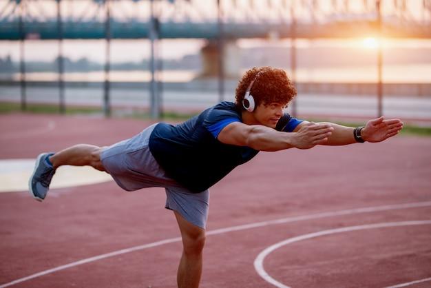 強いフィットの若い男が早朝外でバランス運動をします。