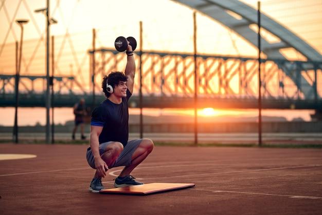 Определите сильного спортивного человека, делающего приседания с весом в руке. ранние утренние тренировки на улице.