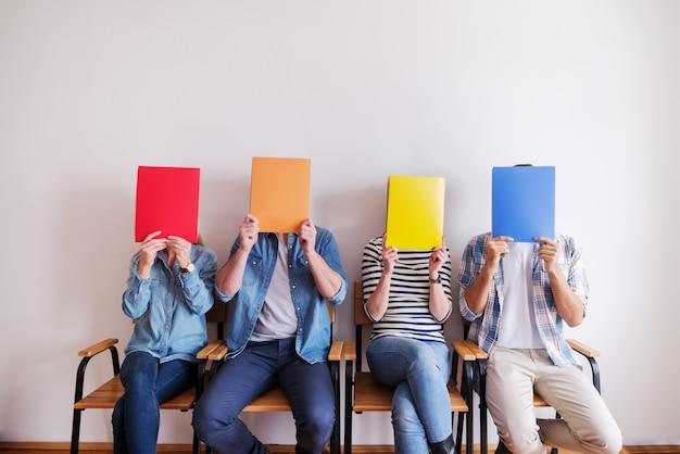 フォルダーを顔の前で抱え、椅子に座っている人々の小さなグループ。背景の白い壁。ビジネスコンセプトを開始します。