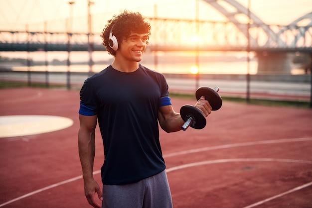 音楽を聴きながら腕に体重を保持している若いスポーティなフィット男。早朝以外のトレーニング。