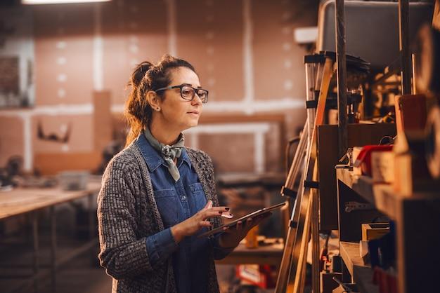 Женский работник плотника используя таблетку пока стоящ в мастерской.