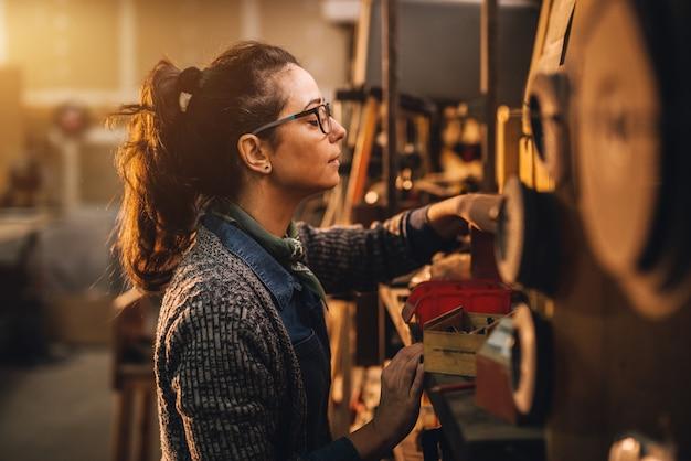 ワークショップやガレージでツールを選択する幸せな魅力的な勤勉な中年のプロ女性大工労働者の肖像画の側面図。
