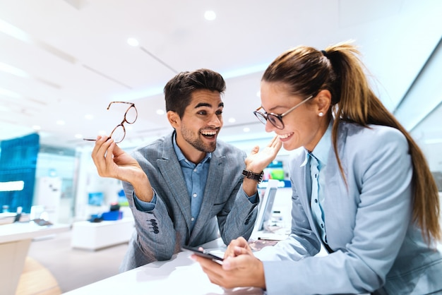 新しいスマートフォンの購入に身を包んだ多文化のカップルの笑顔。電話をしようとしている女性。テックストアのインテリア。