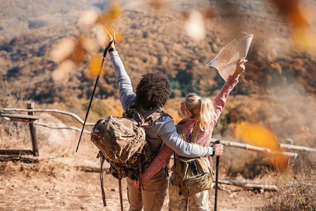 カップルは、空き地の上に立ってビューを見ながら手を抱き締めながら手を挙げます。バックパックの地図を保持している女性。背中を向けた。ハイキングのコンセプトです。