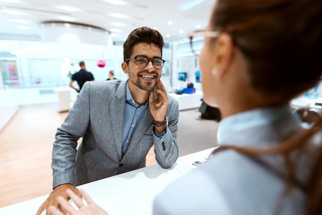 スタンドにもたれながら店員に相談しながらビジネス服を着た混血男。テックストアのインテリア。