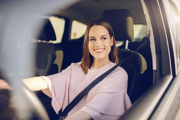 車を運転して歯を見せる笑顔でゴージャスな白人ブルネット。ステアリングホイールに手。