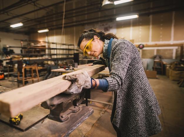 幸せな魅力的な勤勉な中年の肖像画ビュープロの女性大工労働者を探して、ワークショップやガレージで木材を選択します。