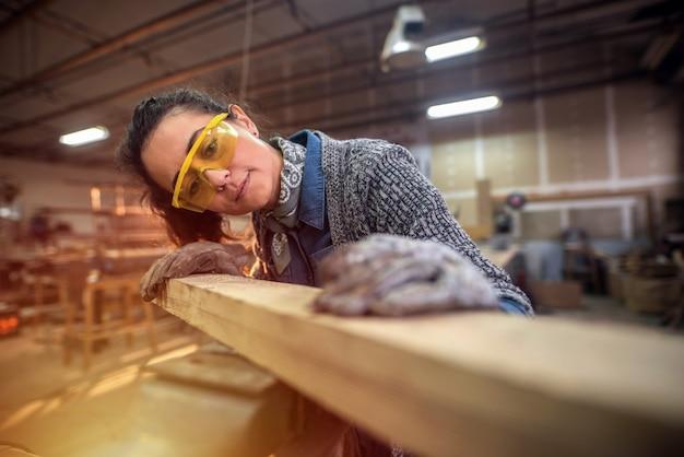 ワークショップで使用している木材の種類を選択している美しい中年の創造的な女性の大工の写真。