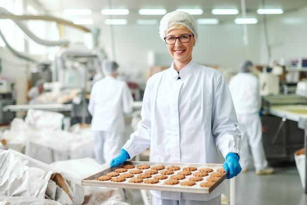 無菌の制服を着た金髪の白人従業員の笑顔と、立ち上がってクッキーを入れたトレイを保持している眼鏡。食品工場のインテリア。バックグラウンドで働く他の従業員。