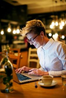 若い女性がカフェでノートパソコンに入力します。眼鏡をかけてラップトップを見て笑っています。