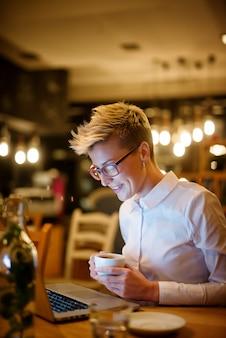 スタイリッシュな自信を持って笑顔の短い髪のブロガー女性がカフェに座っていると夜にラップトップに取り組んでいる間、コーヒーのカップを保持しているの側面図を閉じます。